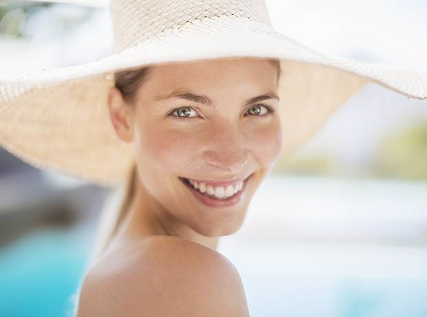 Portrait of smiling woman in sun hat